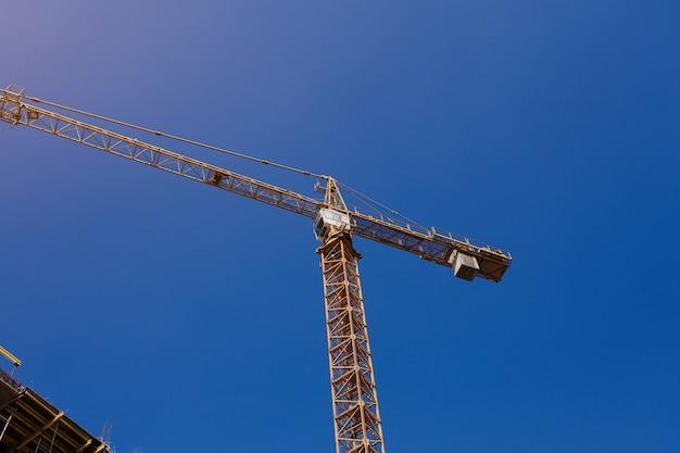 建設現場。青い空を背景に建設用クレーン。