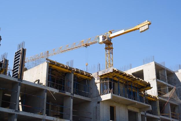 Строительная площадка. конструкция фасада строящегося здания. желтый строительный кран за зданием против голубого неба.