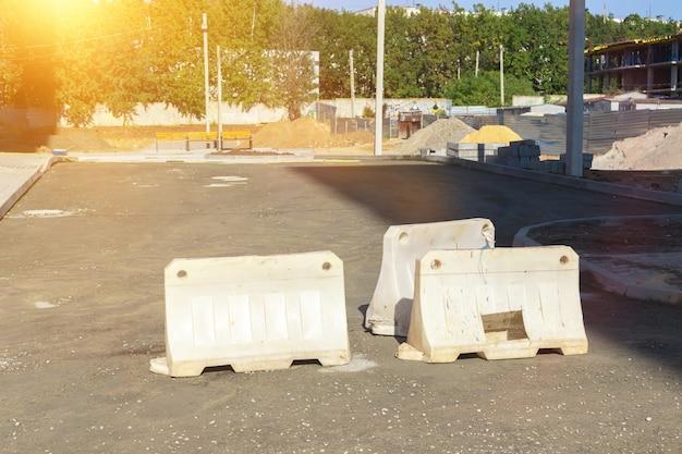 Ограждение строительной площадки, концепция безопасности строительства. защитный забор на дороге в солнечный день, фото дорожных работ