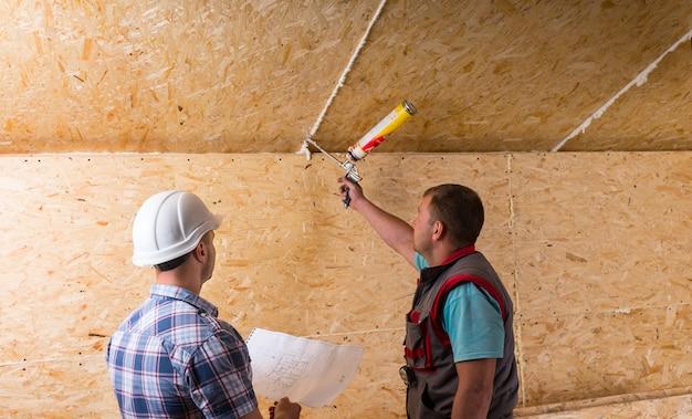 흰색 안전모를 쓴 건설 현장 감독 및 미완성 목재 천장에 코킹을 적용하는 작업자 관찰