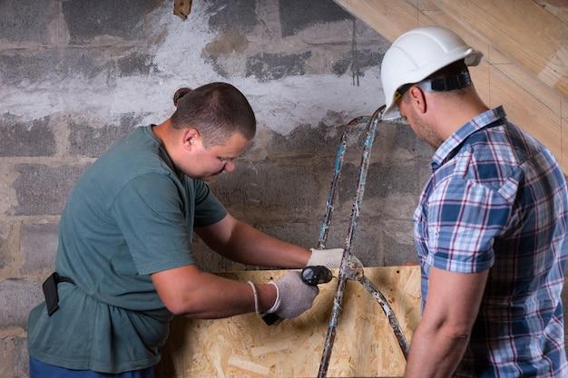 새 집의 미완성 지하실에서 전동 공구 드릴을 사용하여 흰색 안전모 모니터링 작업자를 착용하는 건설 현장 감독