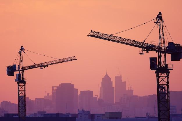 건설 현장에는 두 개의 크레인과 보라색 실루엣이 있습니다.