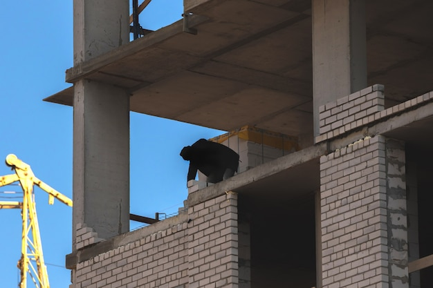 Construction site high rise building under construction and worker silhouette photo
