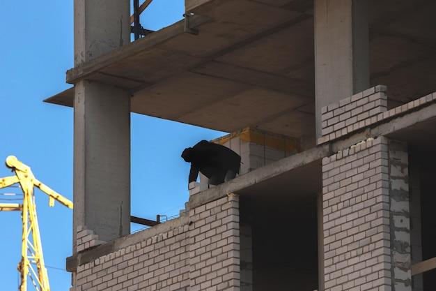 建設中の建設現場の高層ビルと労働者のシルエット写真