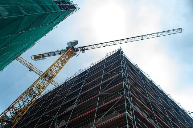 建設現場のジブクレーン。新しい近代的な建物の建設。都市建築。