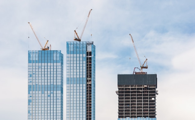 Строительная площадка зданий небоскребов и кранов против неба.