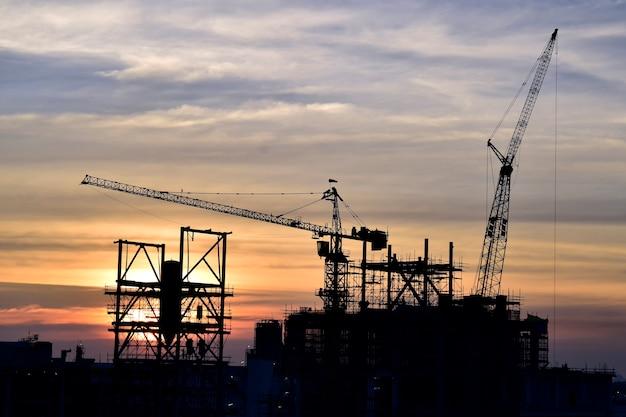 Строительная площадка. башенные краны силуэта строят большие жилые здания на строительной площадке.