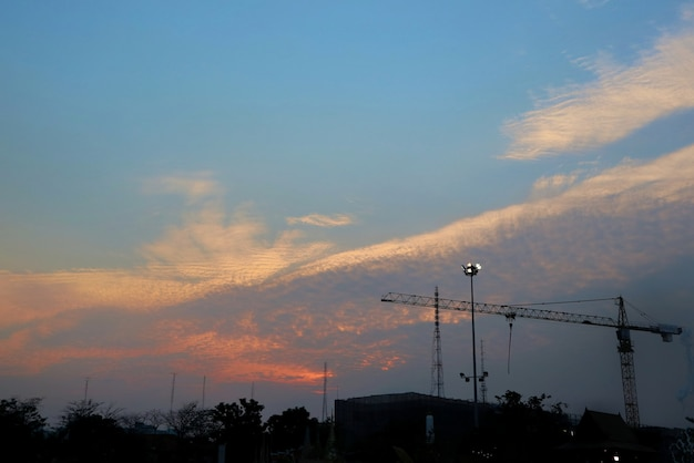 Construction site silhouetted against colorful evening sky with blue sky and clouds. industrial.
