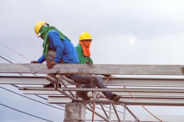 In the construction site, the welding workers at work at top roof.