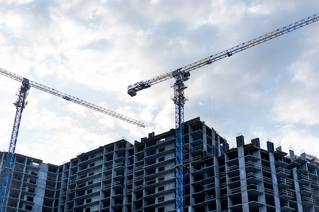 Construction site with construction crane and cloudy sky on background