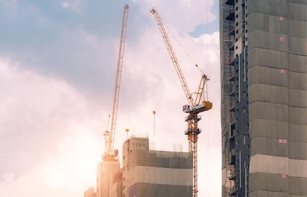 Строительная площадка с краном и зданием. индустрия недвижимости. подъемное оборудование мотовила использования крана на строительной площадке. строительная площадка многоквартирного дома. строительный кран работает против неба.