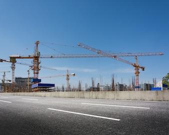 青い空を背景にクレーンと建設現場