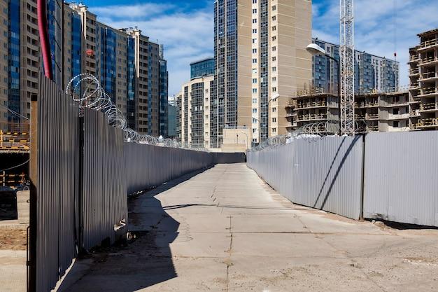 건설 중인 주거용 아파트 단지를 배경으로 울타리와 콘크리트 도로가 있는 건설 현장. 산업 위험 구역의 보기입니다. 주택 개조의 개념입니다. 복사 공간
