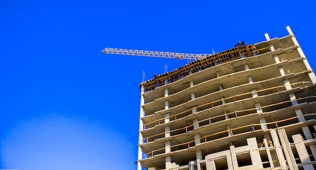 青空の背景写真に高層建設用クレーンのある建設現場