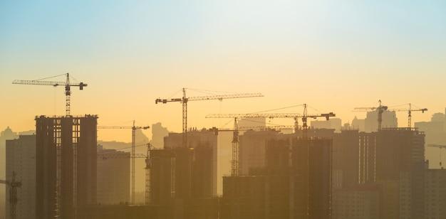 일몰에 도시에 산업 크레인이 있는 건설 현장