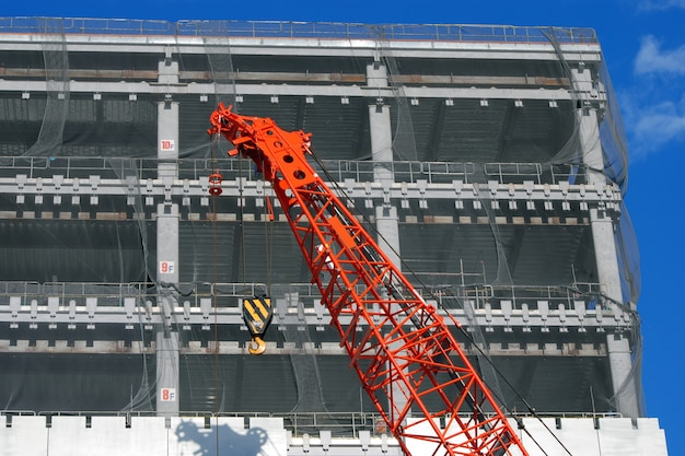 Construction site with rising up building and red crane foreground