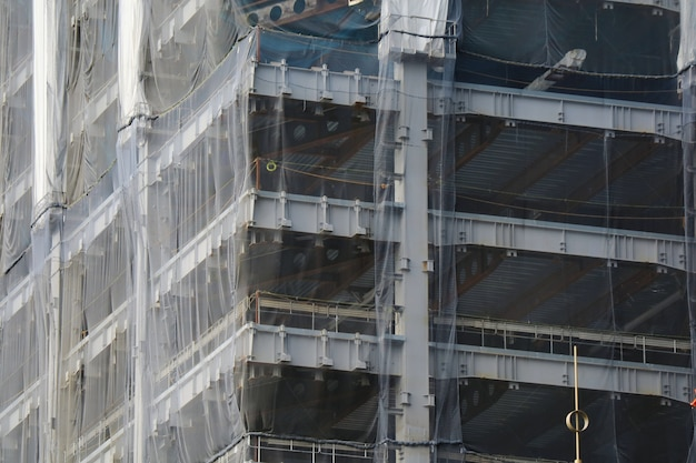 Construction site with scaffolding and grey cover at the building.