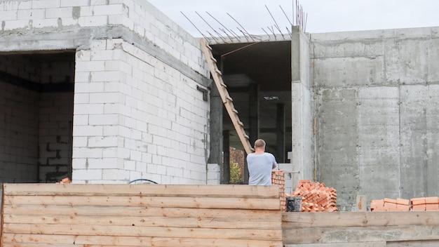 Строительная площадка с рабочими. строящиеся современные здания за деревянным забором. строительные работы. монолитное одноэтажное здание из бетона и красного кирпича.