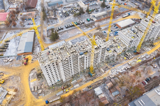 A construction site with yellow tower construction cranes is a concept. housing construction.