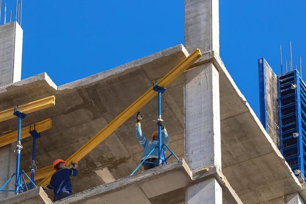 青空を背景に建設中の高層ビルの建設現場の労働者背景写真