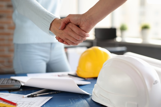 Over construction sketches, designer and client shake hands with each other. conclusion of transactions with real estate concept