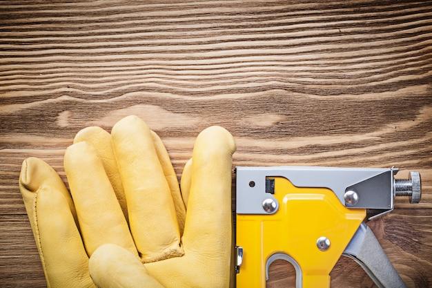 Строительный степлер пара защитных перчаток на деревянной доске