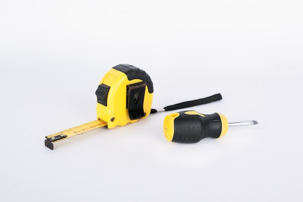 Construction tape measure meter and screwdriver on a white background. repair preparation concept. building .