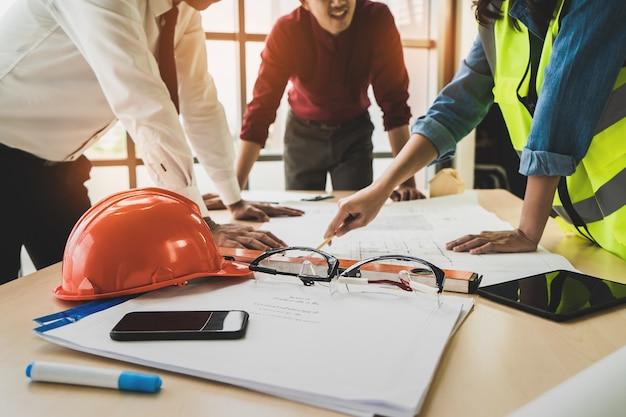 ビジネスマンのエンジニアと建築家との建設チームは、建築計画で作業台についてブレインストーミングしています