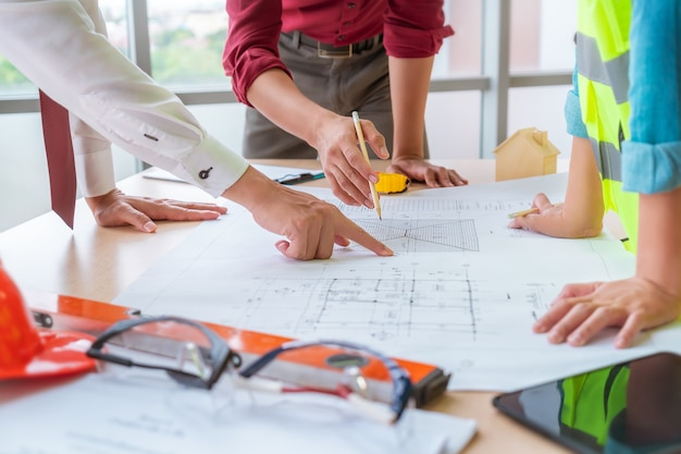 Construction team with business man engineer and architect is brainstorming on working table with building plan