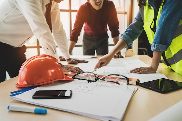 Construction team with business man engineer and architect is brainstorming on working table with building plan Premium Photo
