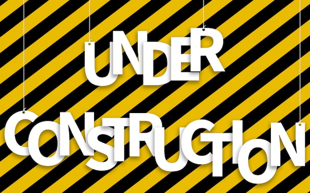 Under construction text hanging on ropes on yellow and black