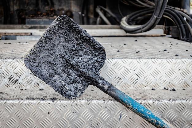 Строительный инструмент для дорожных работ. лопата для укладки асфальта крупным планом. асфальтирование дорог.