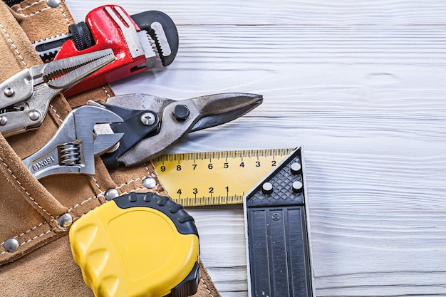 Construction tools in building belt on wooden board maintenance concept