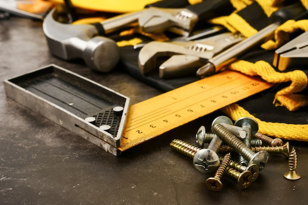 Construction tools on concrete texture background.