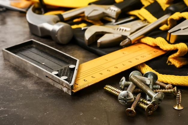 Construction tools on concrete texture background.