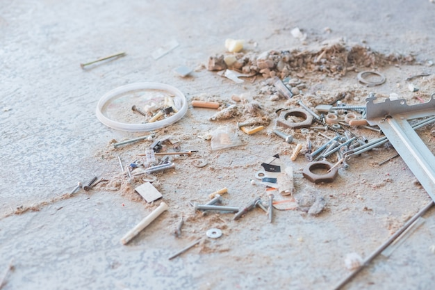 Construction tools, construction debris, a pile of concrete stones, dust, rubble, fragments of walls of buildings, metal inserts. floor of the destroyed building