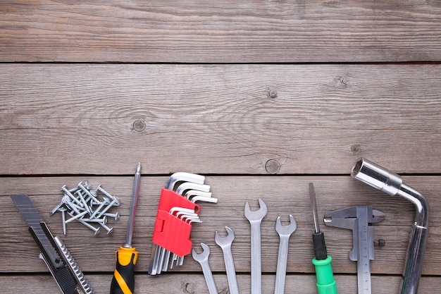 Construction tools on a grey wooden desk, copy space
