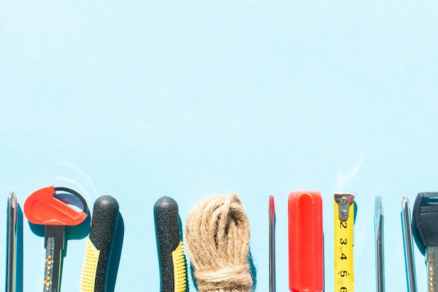 Construction tools in a row on light blue background