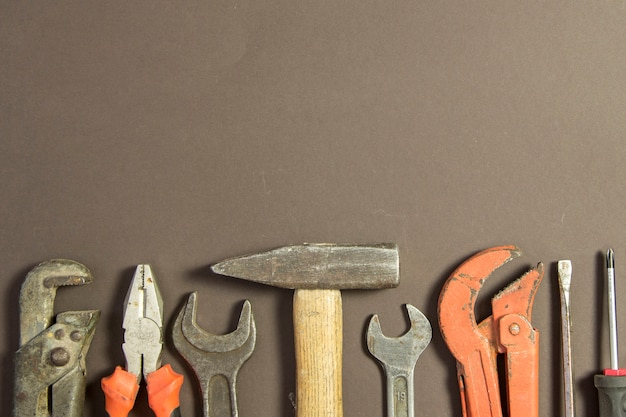 Construction tools on textured grunge paper consisting of pipe wrench, screwdriver, metal, hammer and free copy space on the top