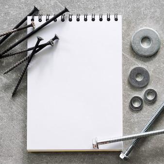 건설 도구. 나사, 너트 및 볼트는 구체적인 배경에 빈 나선형 바운드 참고 책 종이 주위에 정렬됩니다. 수리, 주택 개선 개념. 텍스트, 평면도, 평면 배치를위한 여유 공간.