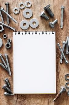 건설 도구. 나사, 너트 및 볼트는 나무 배경에 빈 나선형 바운드 참고 책 종이 주위에 배열. 수리, 주택 개선 개념. 텍스트, 평면도, 평면 배치를위한 여유 공간.