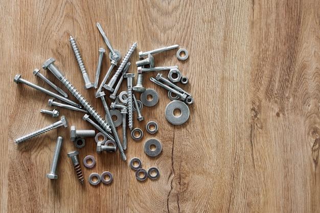건설 도구. 나무 배경에 나사, 너트와 볼트. 수리, 주택 개선 개념. 텍스트, 평면도, 평면 배치를위한 여유 공간.
