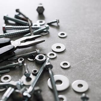 건설 도구. 구체적인 배경에 펜 치와 나사, 너트 및 볼트. 수리, 주택 개선 개념. 텍스트, 평면도, 평면 배치를위한 여유 공간.