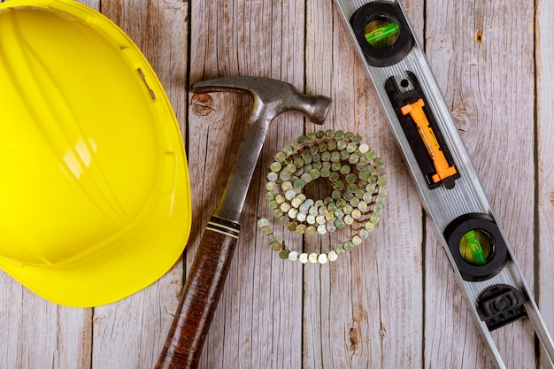 Строительные инструменты с молотком, гвоздями и уровнем на строителе в шлеме плоской планировки сверху