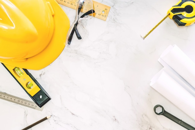 Construction tools with helmet safety on white marble background