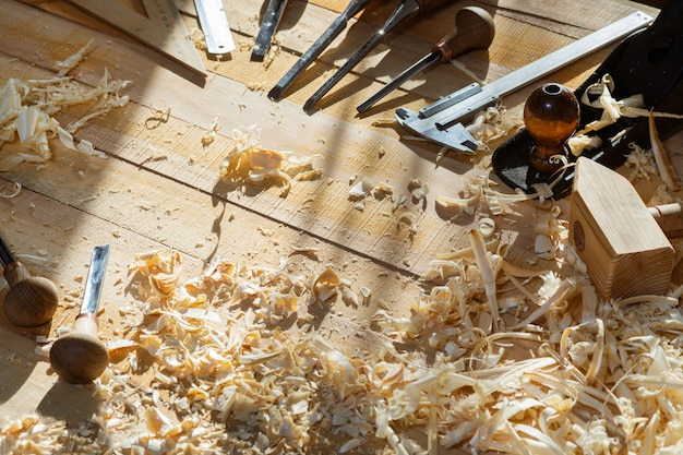 Construction tools on wooden table with shavings