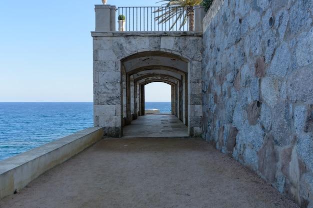 Construction with arch rocky coast & translucent sea