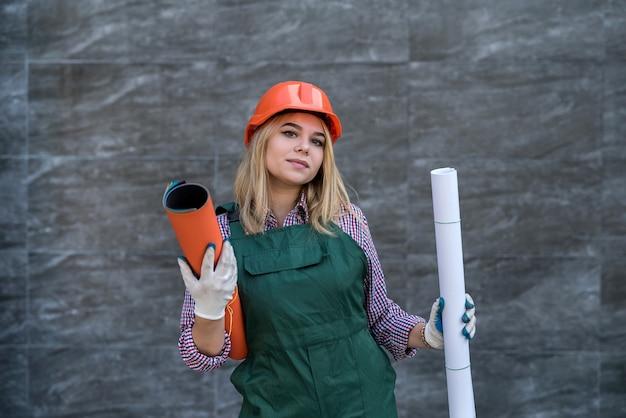 赤い制服とヘルメットの建設女性、保護手袋はカメラのポーズをとり、アパートを修理する準備をします