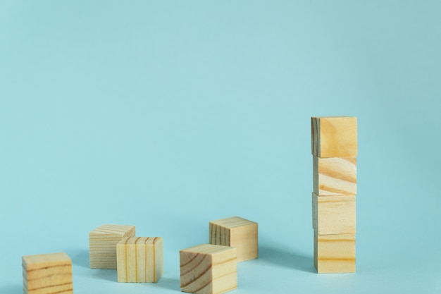 Construction of wooden cubes on blue background with copy space. mockup composition for design