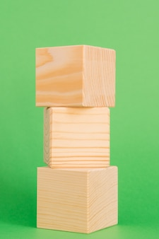 Construction of wooden cubes on green background with copy space. mockup composition for design